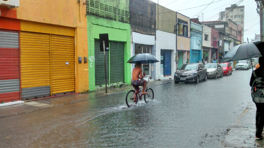 Cyclist with umbrella tries to keep dry in downtown Recife during downpour. Photo: Athas Zafiris